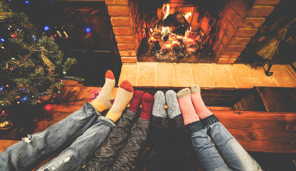 Family with warm socks sitting by the fireplace