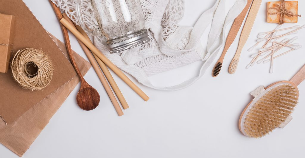 Sustainable products: reusable bags, bamboo toothbrush, and paper straws.