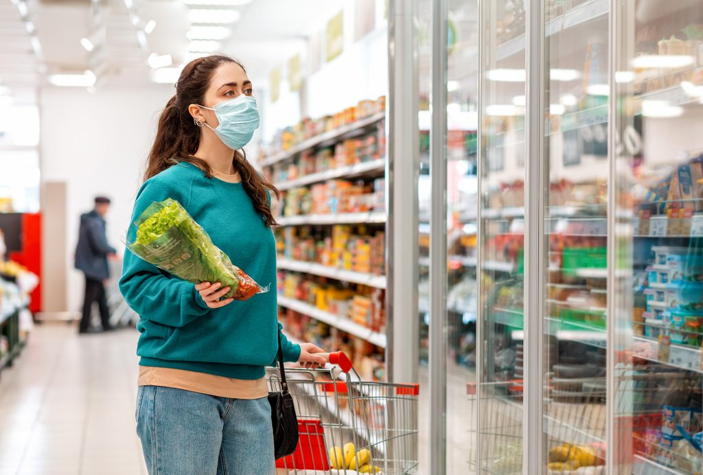 Woman shopping at a store with a mask during covid-19