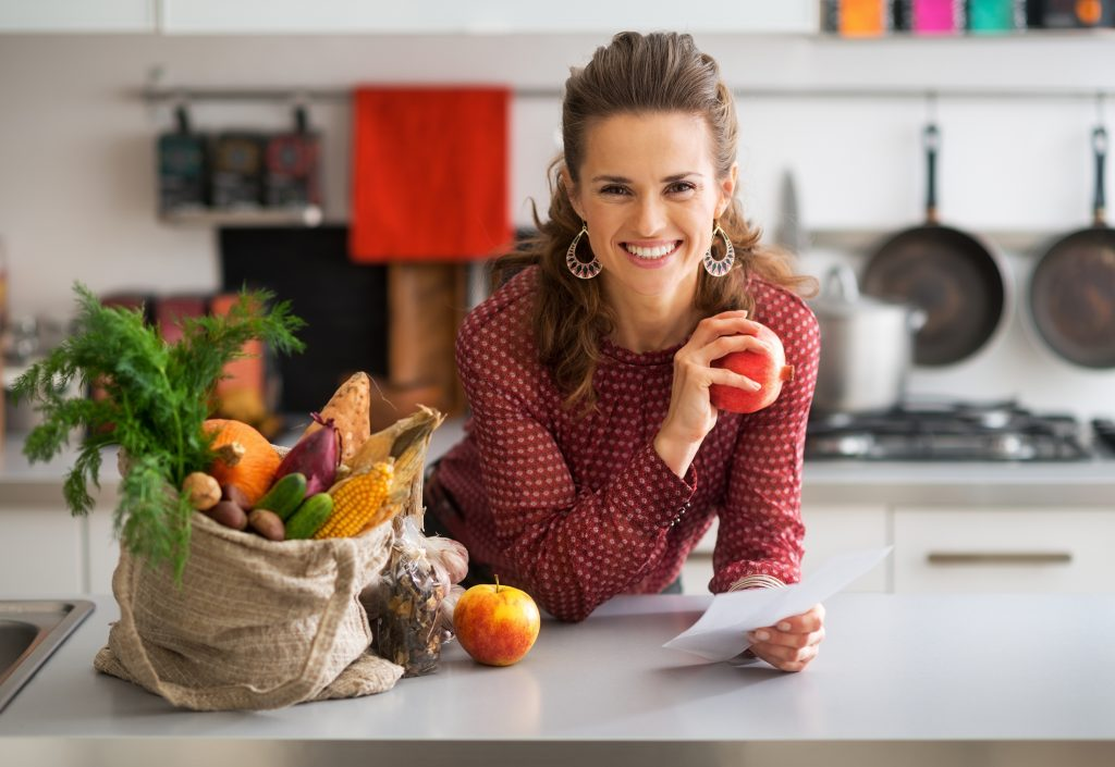 woman in a kitchen after a shopping trip