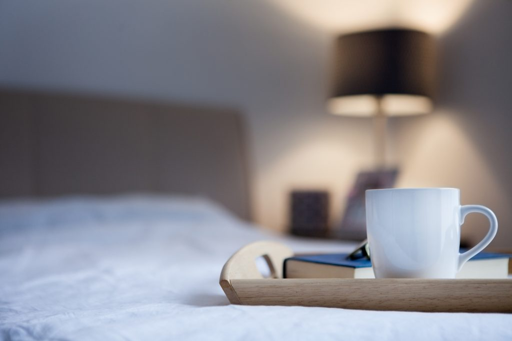 cup of tea and a book on bed