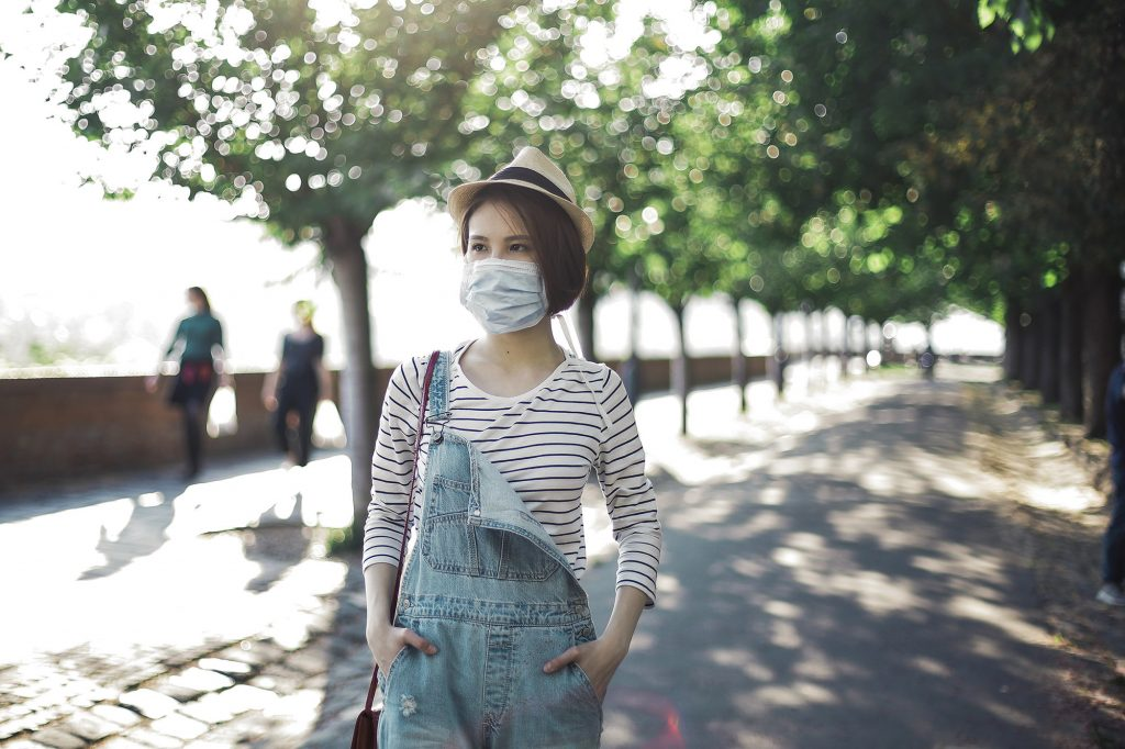 woman walking outside with a mask on