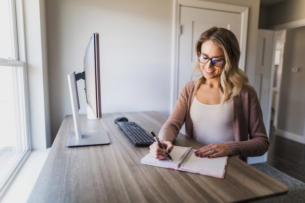 Young woman with glasses working on a standing desk