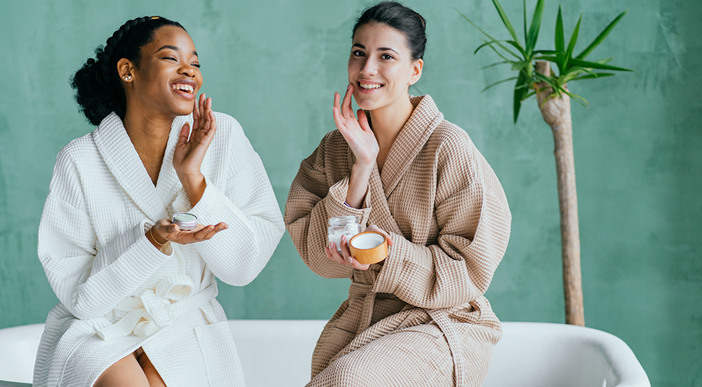 Two women applying skincare