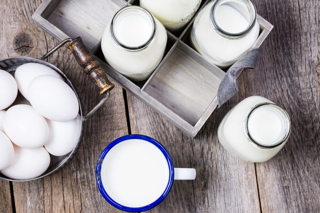 Close up of bottles with milk  and eggs in basket.