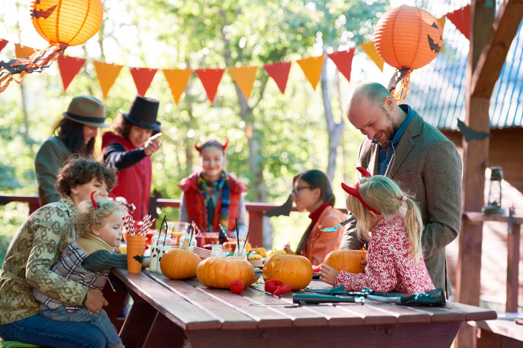 Adults and children carving pumpkins outdoors.
