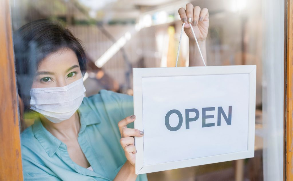 Small business owner with face mask hanging open sign for her store.