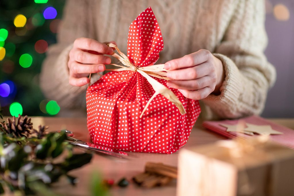 Woman Wrapping Christmas Gift In Eco Friendly Reusable Sustainable Cloth
